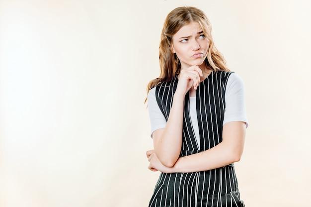 Retrato de uma menina pensativa e sombria, sobre um fundo claro, uma carranca sombria