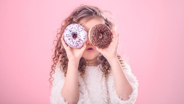 Retrato de uma menina pequena surpresa com donuts