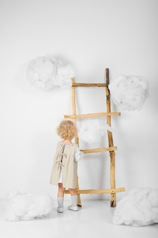 Retrato de uma menina perto da escada no meio das nuvens em um fundo branco