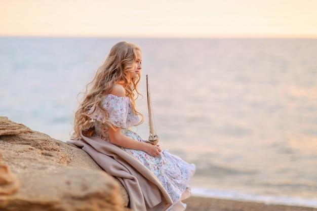 Retrato de uma menina perto do mar, sentado nas rochas com um navio de brinquedo nas mãos.