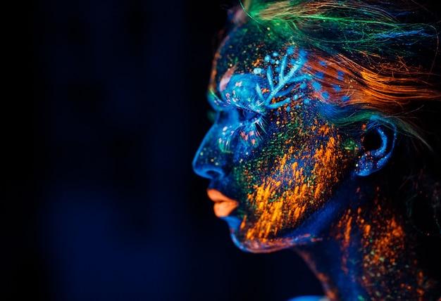 Retrato de uma menina pintada em pó fluorescente.