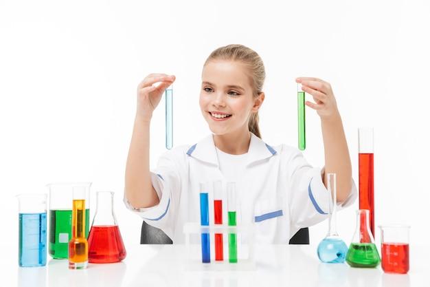 Retrato de uma menina positiva com jaleco branco, fazendo experimentos químicos com líquido multicolorido em tubos de ensaio isolados sobre uma parede branca