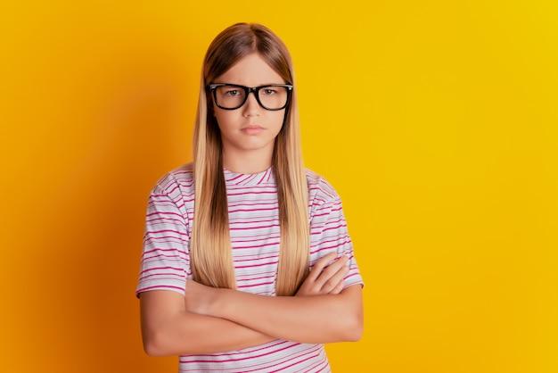 Retrato de uma menina pré-adolescente ofendida com os braços cruzados, isolado sobre um fundo amarelo