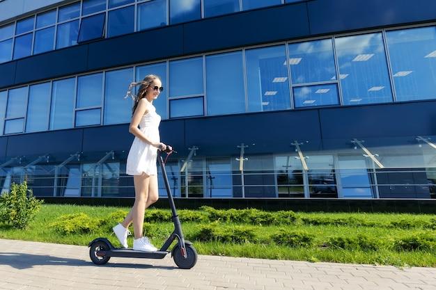 Retrato de uma menina que anda de scooter elétrica na cidade