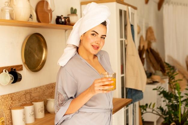 Retrato de uma menina que bebe suco de laranja na cozinha dela. ela desintoxica o corpo, o conceito de nutrição adequada