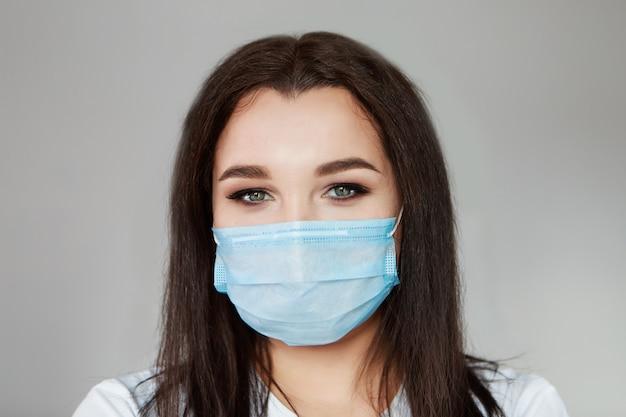 Retrato de uma menina que cobriu o rosto com uma máscara. olhos assustados do paciente. o conceito de quarentena, auto-isolamento, proteção contra coronavírus, vírus, medo de doenças, tratamento, remédios