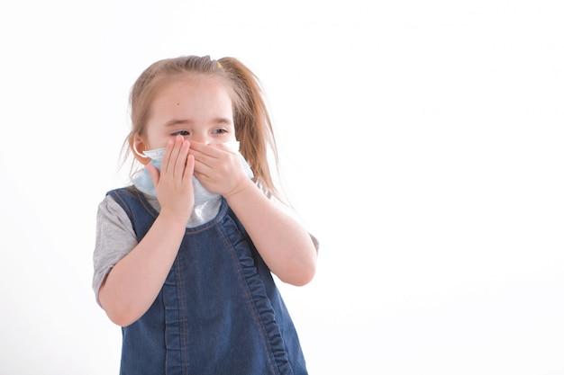 Retrato de uma menina que cobriu o rosto com uma máscara. olhos assustados do paciente.