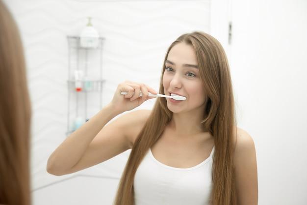 Retrato de uma menina que limpa os dentes