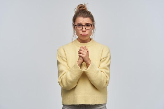 Retrato de uma menina rezando, triste, com cabelos loiros reunidos em um coque. vestindo óculos e suéter amarelo. mantém as palmas das mãos juntas, faz beicinho e implora. olhando para a câmera, isolada sobre uma parede branca