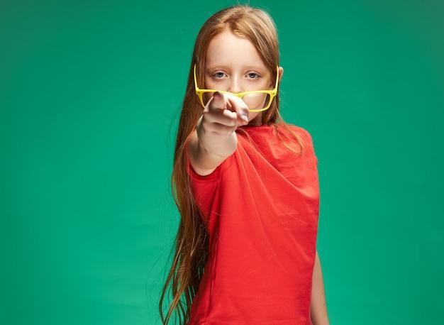 Retrato de uma menina ruiva, apontando para a frente