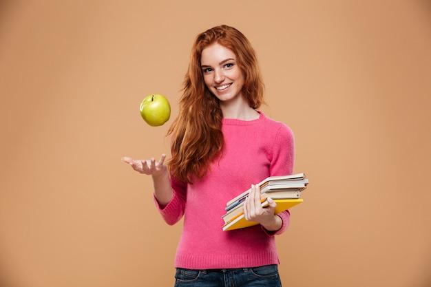 Retrato de uma menina ruiva bonita amigável, segurando a maçã e livros