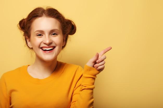 Retrato de uma menina ruiva bonita apontando o dedo sobre um fundo amarelo