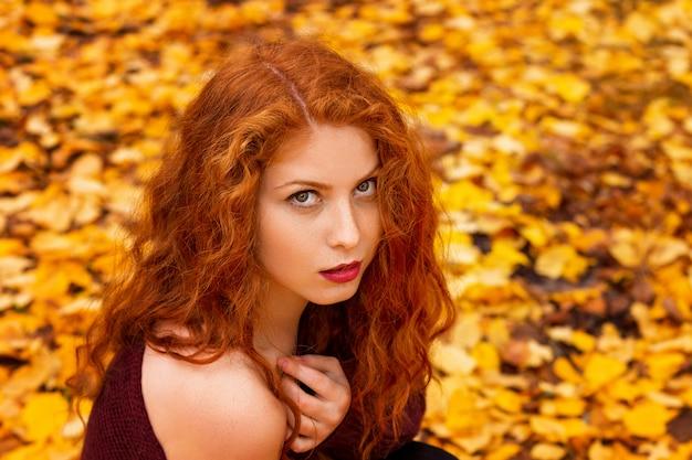 Retrato de uma menina ruiva bonita em folhas amarelas