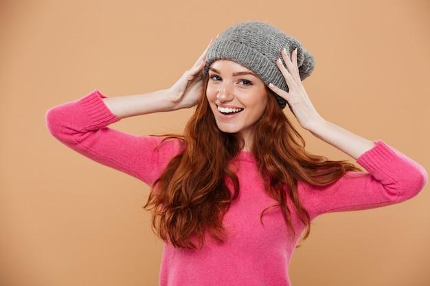 Retrato de uma menina ruiva bonita feliz com chapéu de inverno