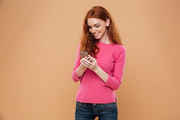 Retrato de uma menina ruiva bonita feliz mensagens de texto em smartphone