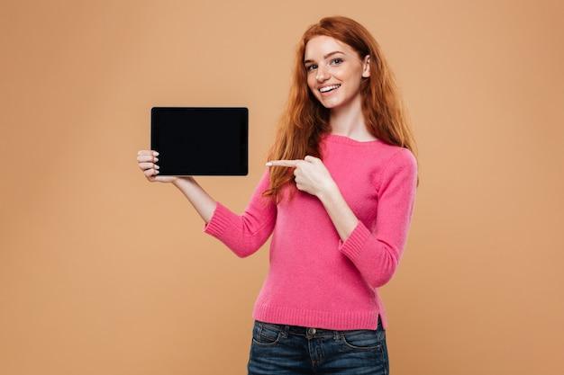 Retrato de uma menina ruiva bonita sorridente, apontando o dedo para tablet digital