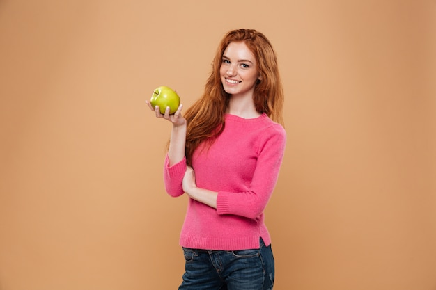 Retrato de uma menina ruiva bonita sorridente segurando a maçã