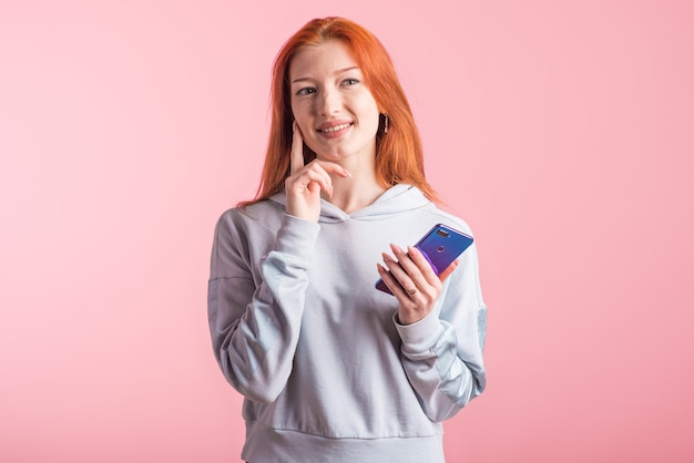 Retrato de uma menina ruiva pensativa com um smartphone nas mãos no estúdio em um fundo rosa