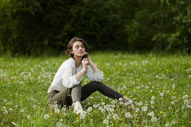 Retrato de uma menina sentada em um campo na grama primavera entre flores-leão.