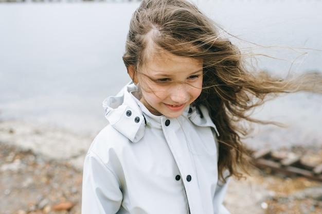 Retrato de uma menina smilling perto do mar na capa de chuva