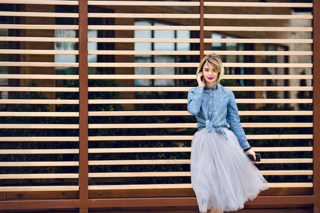 Retrato de uma menina sonhadora com cabelo loiro curto voador e lábios cor de rosa brilhantes, ouvindo música em um smartphone com madeira listrada recusa