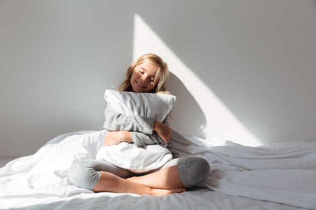 Retrato de uma menina sorridente, abraçando o travesseiro