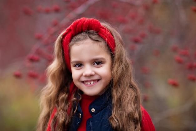 Retrato de uma menina sorridente com cabelos longos em uma árvore de rowan