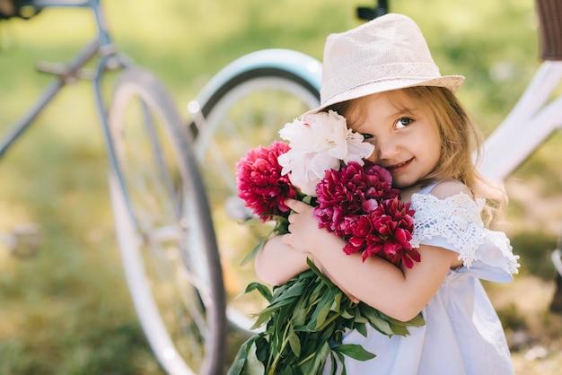 Retrato de uma menina sorridente com grande buquê de flores na te verde backgroud