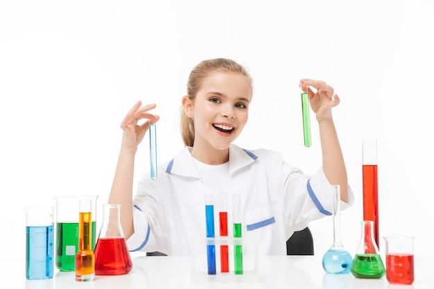 Retrato de uma menina sorridente com jaleco branco fazendo experimentos químicos com líquido multicolorido em tubos de ensaio isolados sobre uma parede branca