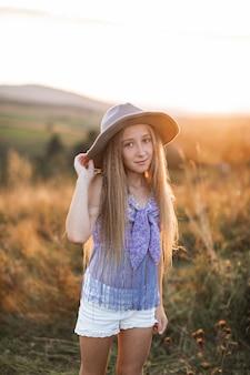 Retrato de uma menina sorridente com longos cabelos loiros com chapéu marrom, em pé no campo de verão