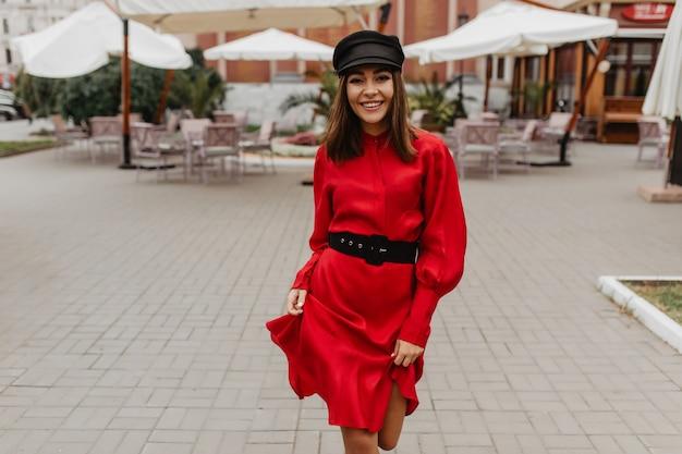 Retrato de uma menina sorridente com olhos escuros e cabelos castanhos. a senhora com vestido de seda vermelha caminha com facilidade pela rua parisiense