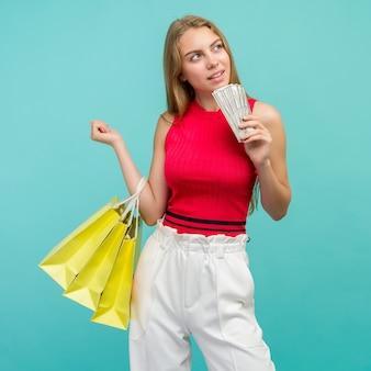 Retrato de uma menina sorridente com sacolas de compras e um monte de dinheiro, notas dos eua