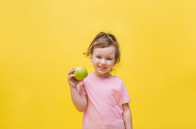 Retrato de uma menina sorridente com um rabo de cavalo em uma camiseta rosa com uma maçã verde na mão