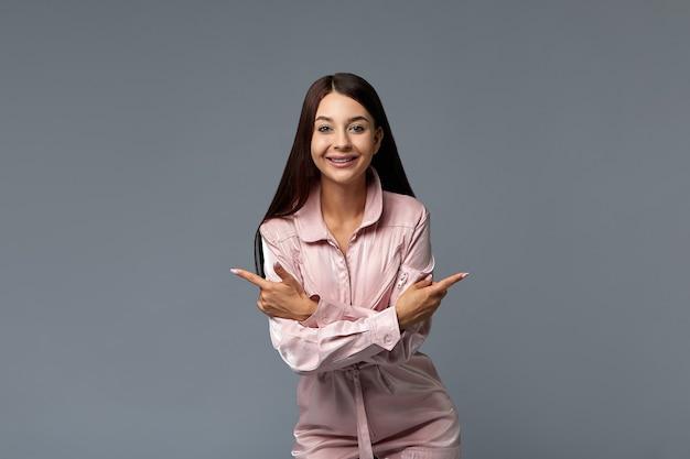 Retrato de uma menina sorridente da moda de macacão rosa, apontando o dedo para o espaço vazio da cópia. copie o espaço, plano de fundo cinza. conceito de moda.