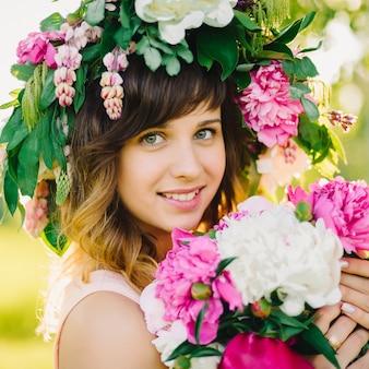 Retrato de uma menina sorridente e feliz com uma coroa de flores e um buquê de peônias