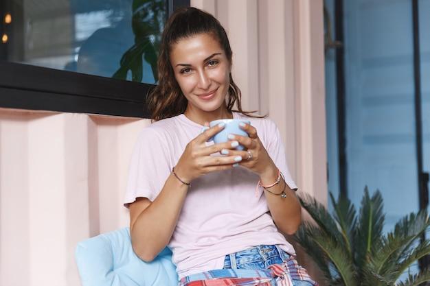 Retrato de uma menina sorridente e relaxada, bebendo chá na varanda.