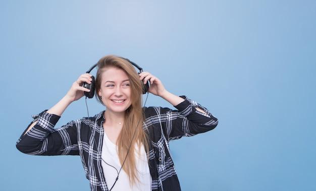 Retrato de uma menina sorridente em roupas casuais, de pé sobre um fundo azul, ouvindo música e olhando para longe.