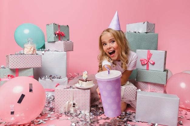 Retrato de uma menina sorridente em um chapéu de aniversário comemorando