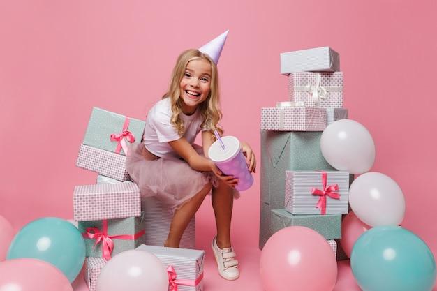 Retrato de uma menina sorridente em um chapéu de aniversário