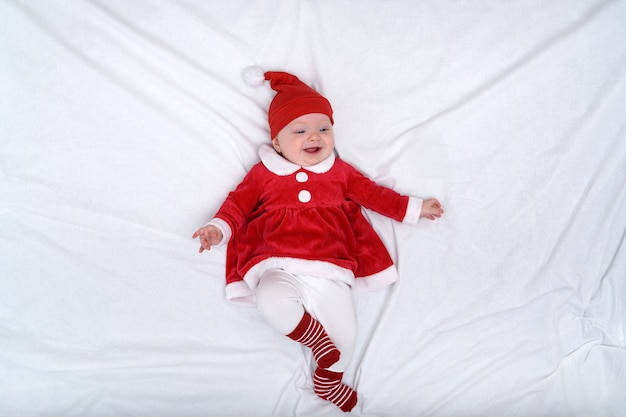 Retrato de uma menina sorridente em um chapéu de papai noel e um vestido vermelho. conceito de natal