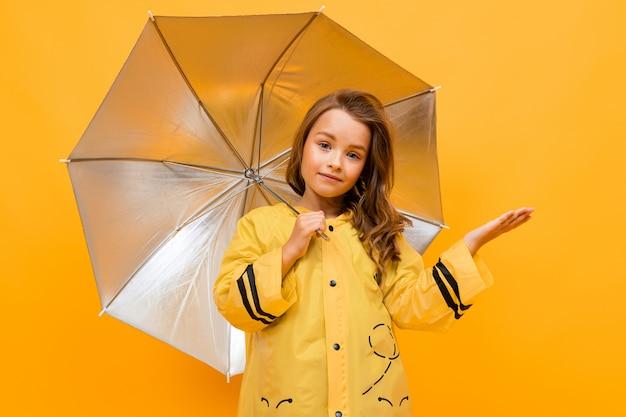 Retrato de uma menina sorridente em uma linda capa de chuva amarela na imagem de uma abelha segurando um guarda-chuva de prata e esticando a mão sobre um fundo amarelo