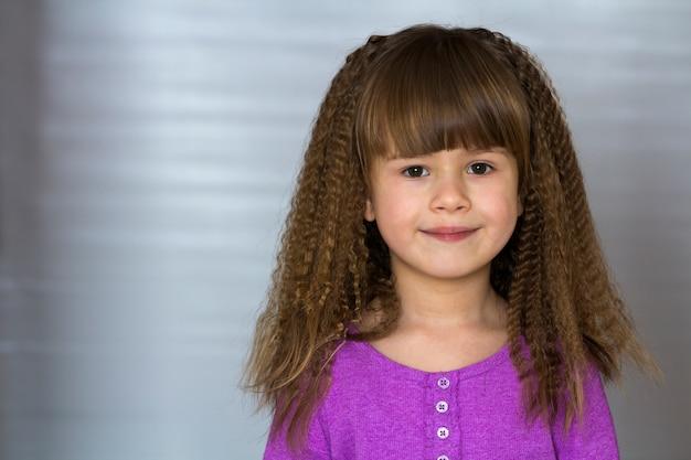 Retrato de uma menina sorridente feliz com belos cabelos grossos