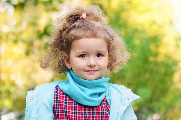 Retrato de uma menina sorridente fofa com cachos em dia de outono.