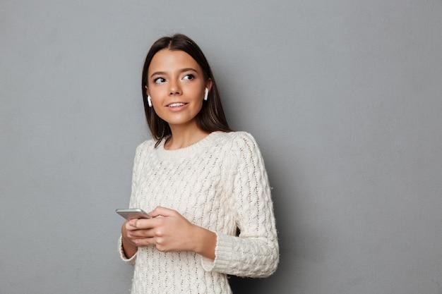 Retrato de uma menina sorridente na camisola ouvindo música