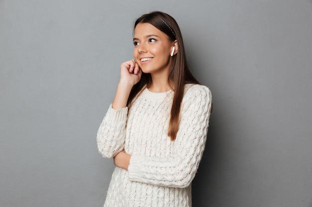 Retrato de uma menina sorridente na camisola usando fones de ouvido sem fio