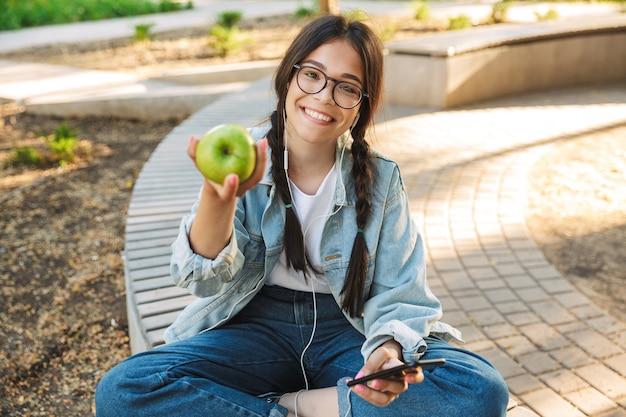 Retrato de uma menina sorridente positivo bonito jovem estudante usando óculos, sentado no banco ao ar livre no parque natural, usando telefone celular conversando, ouvindo música com fones de ouvido, segurando a maçã.