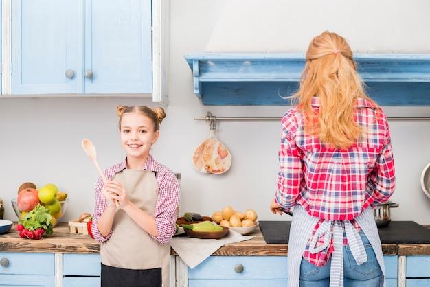 Retrato de uma menina sorridente segurando a colher na mão e sua mãe cozinhar alimentos na cozinha