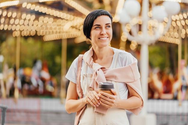 Retrato de uma menina sorridente, segurando a xícara de café na frente do carrossel com iluminação noturna no parque de diversões.