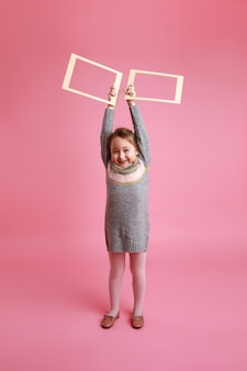 Retrato de uma menina sorridente segurando dois quadros em branco para a maquete em um fundo rosa