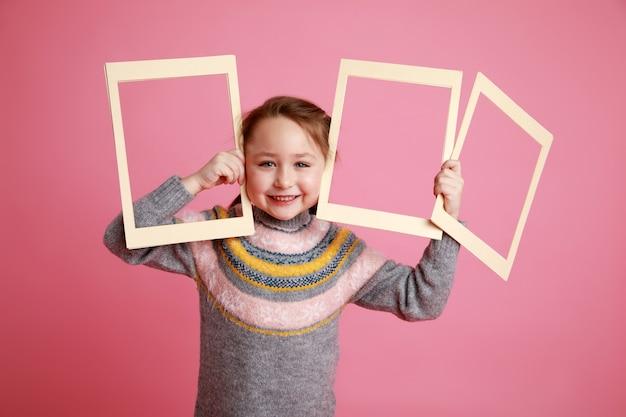 Retrato de uma menina sorridente segurando três molduras em branco para maquete em um fundo rosa